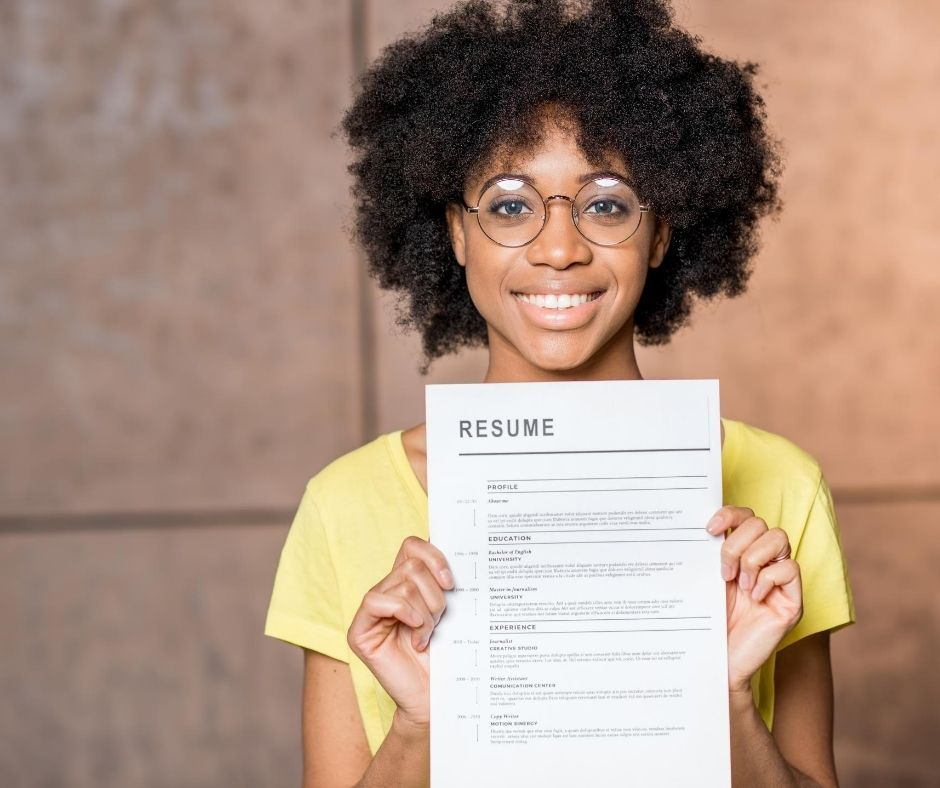 Woman holds her resume and smiles
